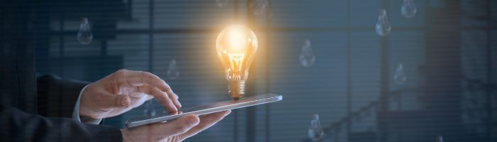 Image of glowing lightbulb over e-device