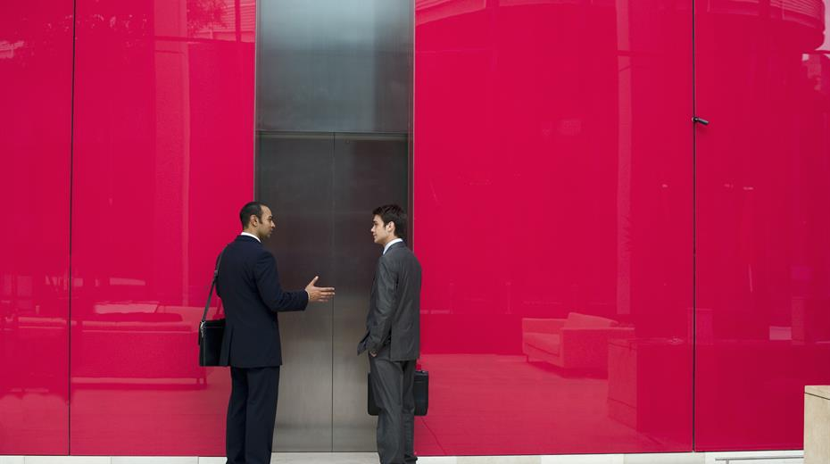 two man talking in front of elevator