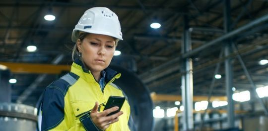 Industrial worker with helmet and mobile phone.